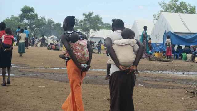 Dos mujeres llevan a la espalda a sus hijos.