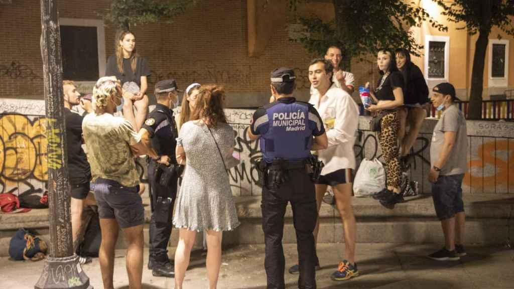 Dos agentes hablan con un grupo de gente, sin llegar a multarles.
