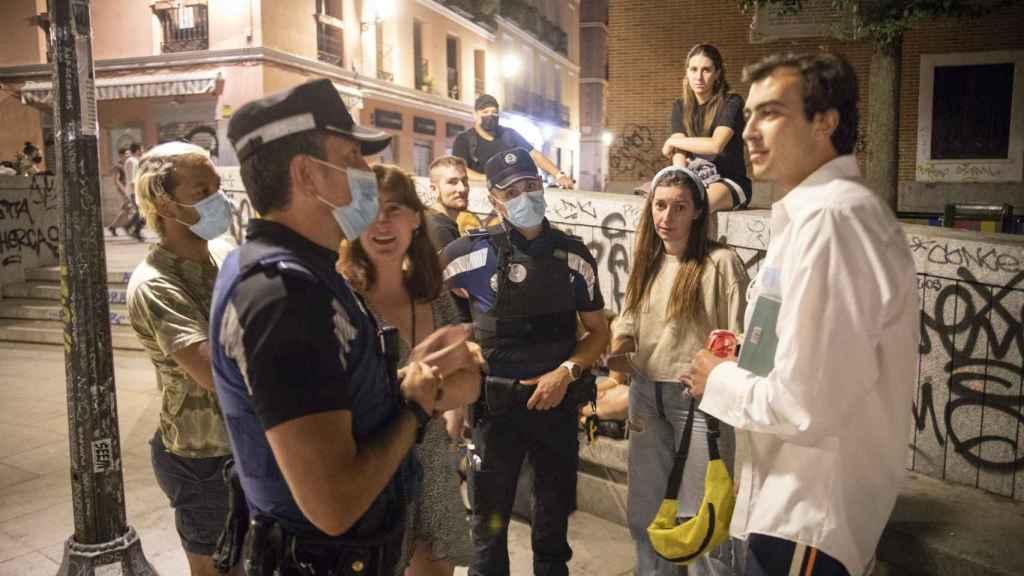 Agentes de la policía municipal hablan con un grupo de gente en la plaza del Dos de Mayo.