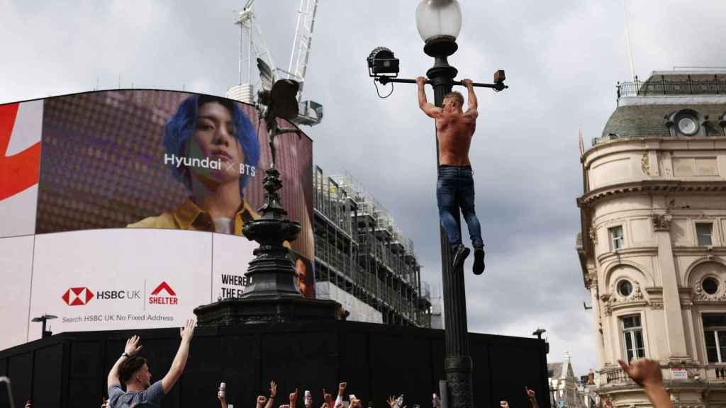 Un aficionado inglés se encarama a una farola en Piccadilly Circus en la previa del Italia - Inglaterra
