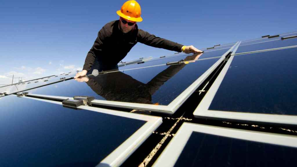 Un operario instalando paneles solares.