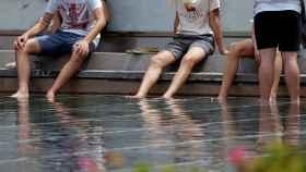 En la foto, un grupo de jóvenes se refrescan en un estanque de Valencia.