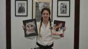 Sandra López posando en el dojo con sus retratos.