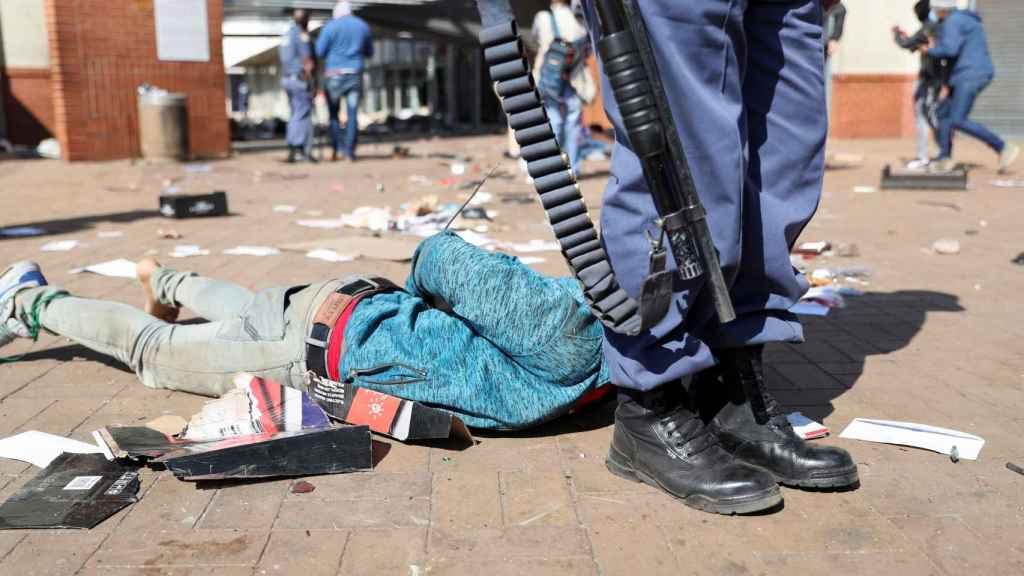 Un hombre arrestado en el suelo al lado de un agente de la policía.