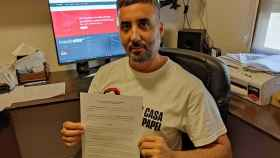 Román, en su casa de Huelva, mostrando la demanda judicial presentada contra MediaStar.