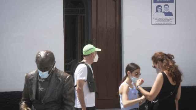 Varios viandantes, con mascarilla, en una calle céntrica de Conil de la Frontera.