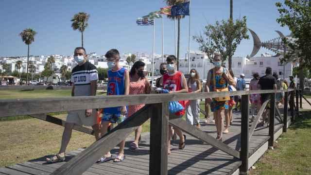 Unos niños bajan a la playa con las mascarillas puestas.