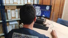 Un agente de la Policía Nacional delante de su ordenador.
