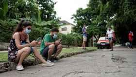 La estudiante Daniela Reyes, junto a su novio, buscando conexión a Internet en un parque de La Habana.