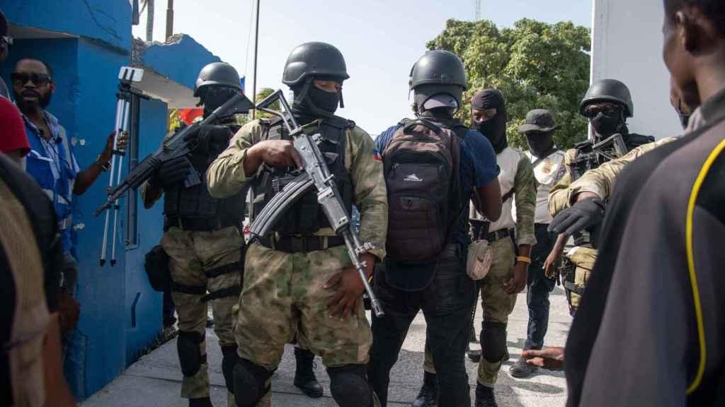 Policías custodian a un grupo de sospechosos de haber participado en el asesinato del presidente haitiano, Jovenel Moise.