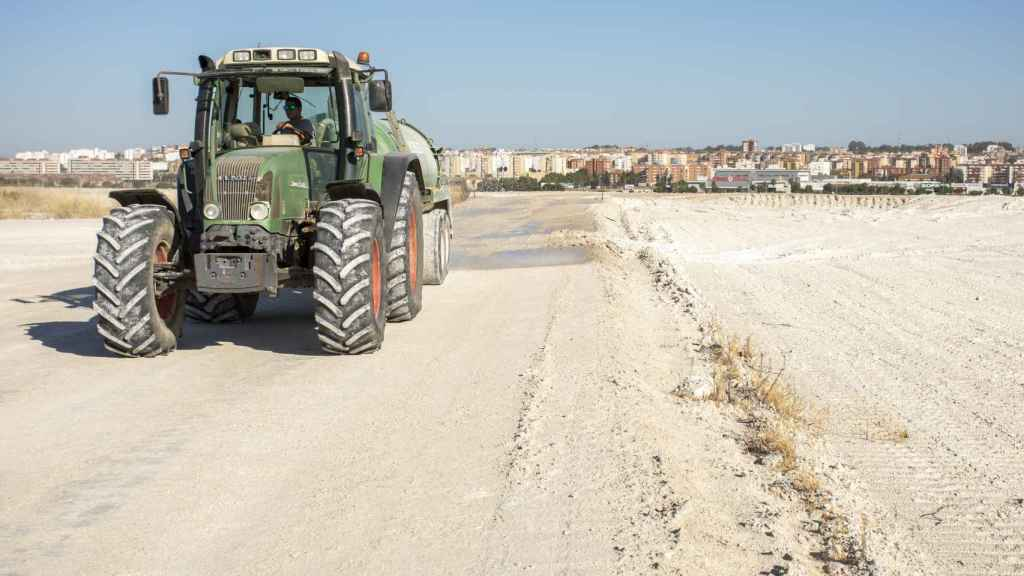Un operario esparce agua para evitar que el polvo se levante con el paso de los vehículos.