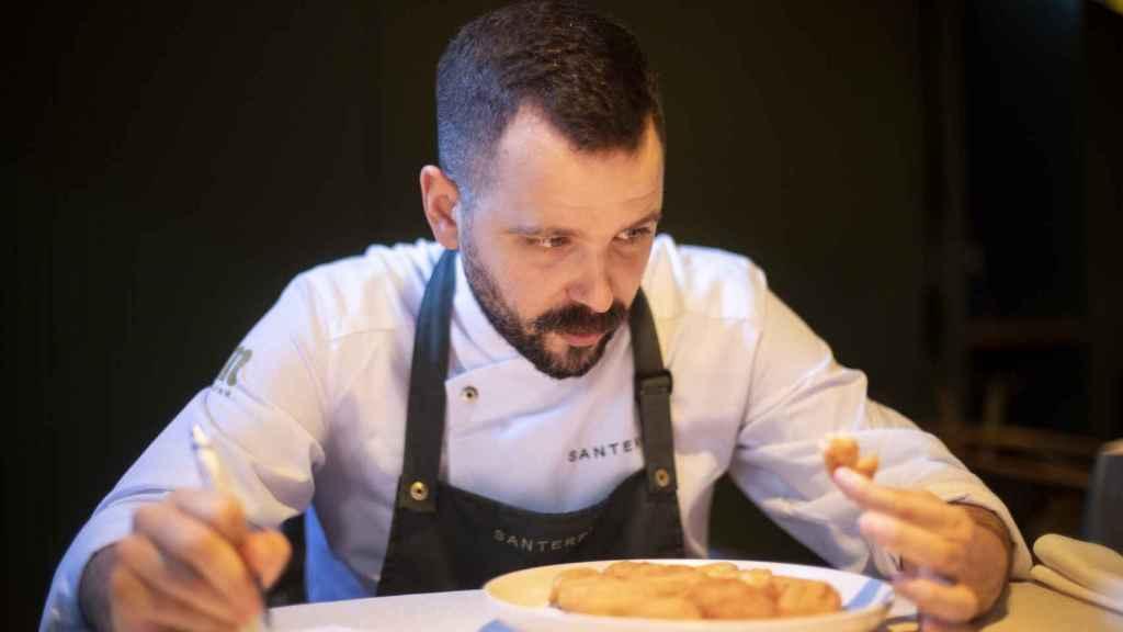 El chef Miguel Carretero, observando el interior de una de las croquetas probadas, mientras apunta todo.