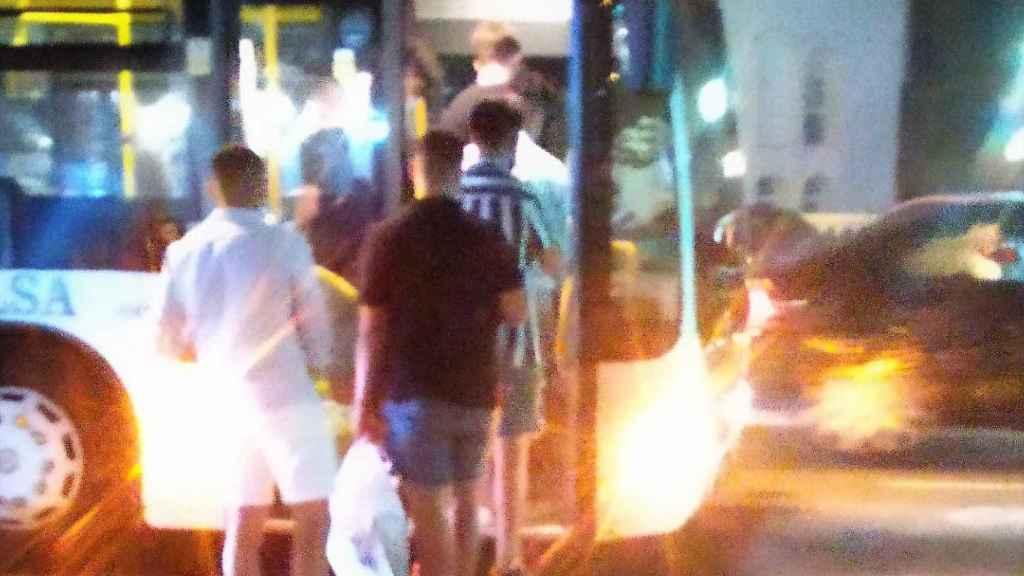 Un grupo de jóvenes se sube al autobús con bolsas con botellas para hacer botellón en la playa.