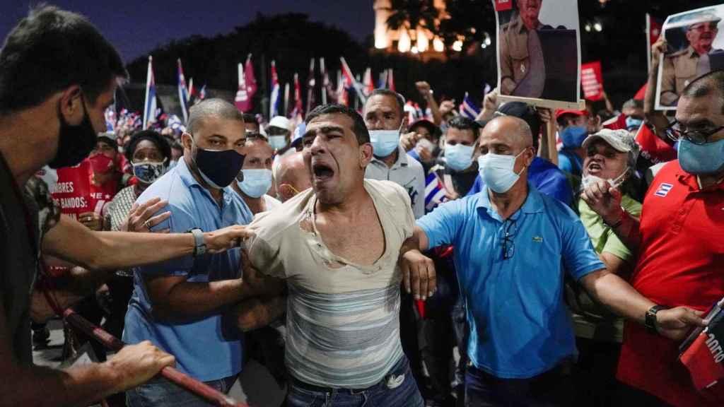 Agentes de paisano detienen a una persona en una manifestación celebrada en La Habana este mismo sábado.