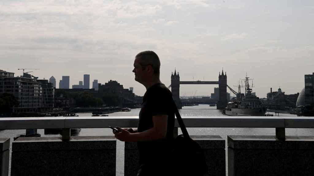 Un ciudadano camino enfrente del Puente de Londres, en Inglaterra, sin mascarilla.