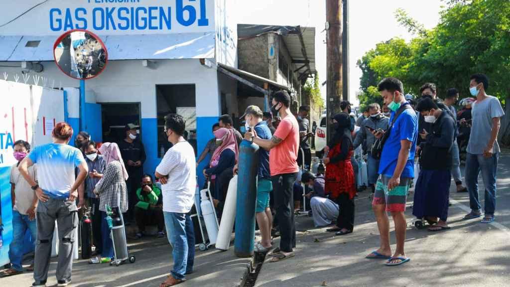Un grupo de personas hace cola ante una fábrica en Yakarta para rellenar sus bombonas de oxígeno.