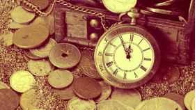 Un reloj junto a monedas de distintas denominaciones.