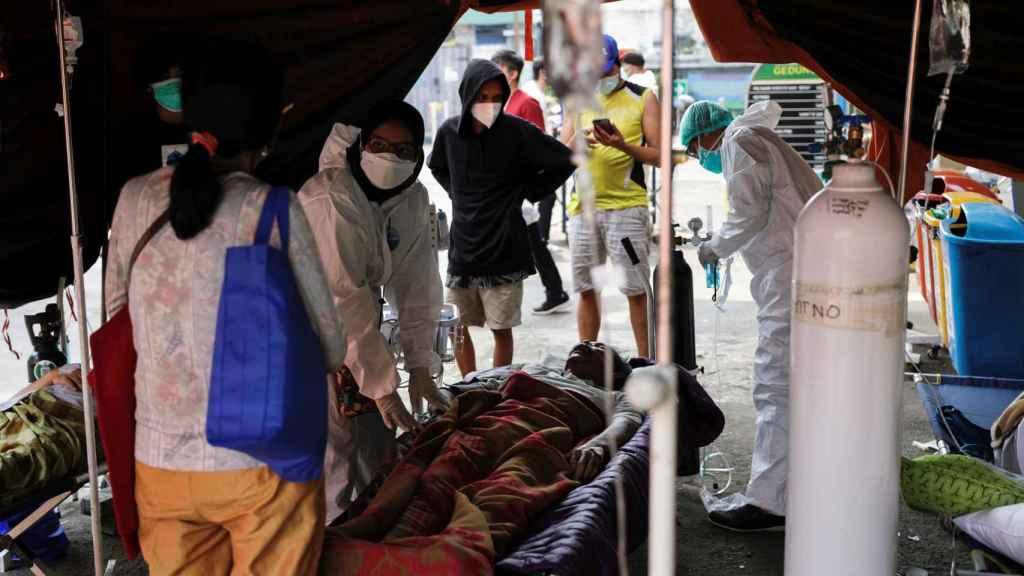 Personal sanitario atiende a un enfermo de Covid en una tienda de campaña en Bekasi, a las afueras de Yakarta.