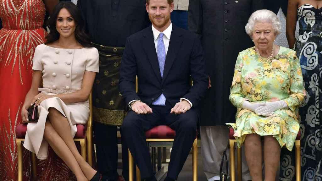 Meghan Markle y el príncipe Harry, junto a la reina Isabel, en la entrega de unos premios, en 2018.