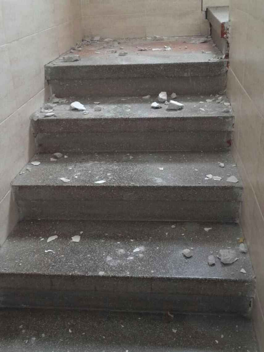 Restos de escombros caídos en la escalera de uno de los edificios de Carranque.