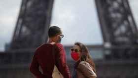 Dos jóvenes con mascarilla delante de la Torre Eiffel.