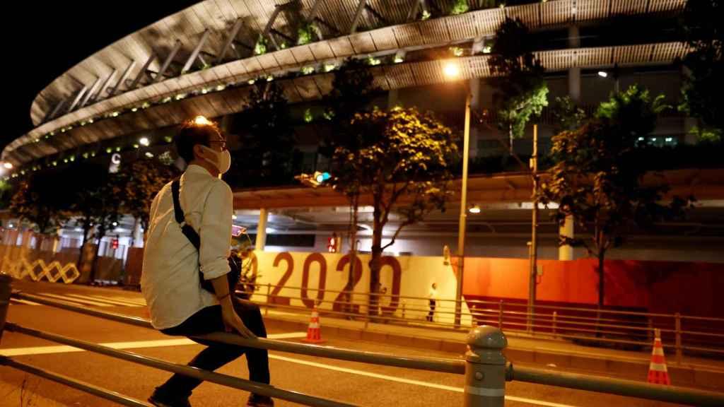 Un hombre llevando una máscara apoyado en frente del Estadio Nacional de Tokio
