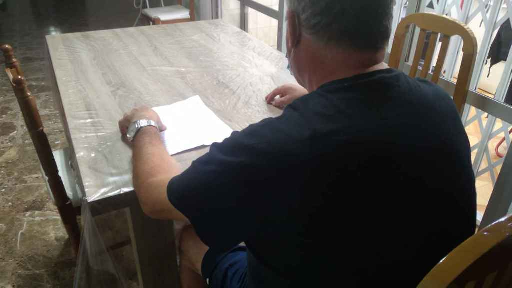 Paco, en el salón de su casa, repasando el parte de alta médica de su hijo.