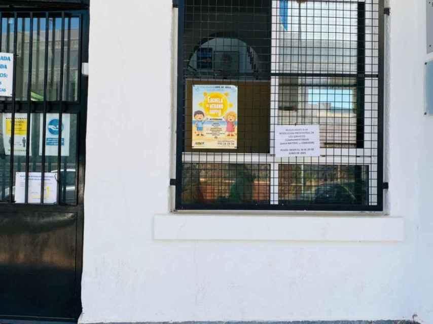 Cartel de la Escuela de Verano en una de las ventanas del colegio público