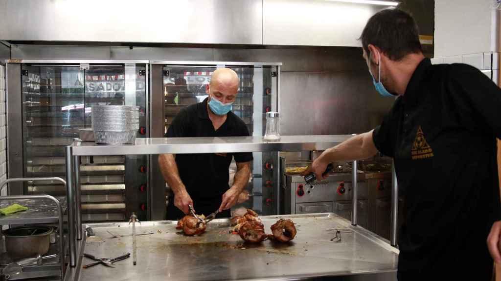 Dos trabajadores de Casa Galván, despachando los pollos asados recién hechos.