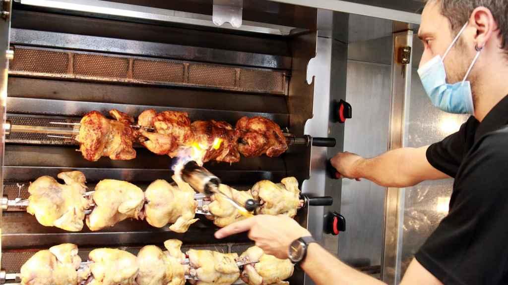 Un trabajador de Casa Galván vigila que los pollos asados queden bien hechos.