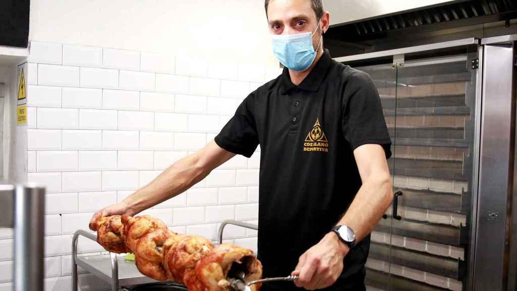 Un trabajador de Casa Galván sujeta varios pollos recién asados.
