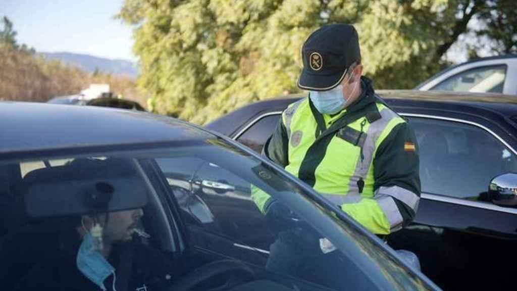 Un agente de la Guardia Civil solicitando a un conductor su documentación.