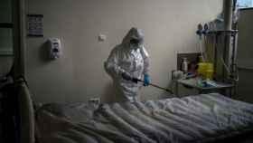 Una trabajadora de la limpieza desinfecta una cama hospitalaria.