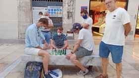 José Antonio orgulloso posando junto a unos desconocidos que juegan al ajedrez.