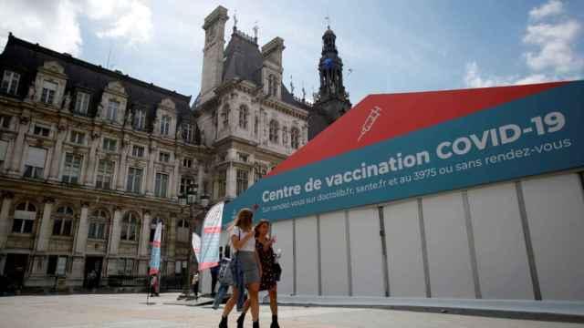 Dos mujeres caminan delante de un centro de vacunación en París.