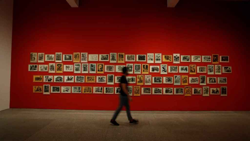 Un visitante pasa delante de la obra 'Estampas de la Revolución mexicana' (1947), una serie de linograbados sobre papel.