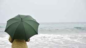 Una mujer con paraguas en la playa.