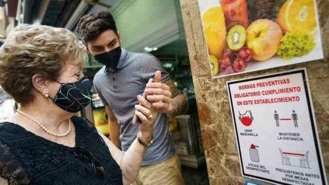 Una clienta muestra su pasaporte Covid para entrar a un establecimiento.