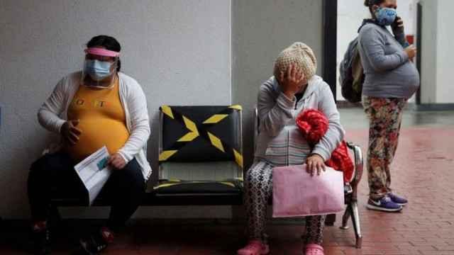 Tres mujeres embarazadas esperan a ser atendidas en Instituto Nacional Materno Perinatal de Lima (Perú).