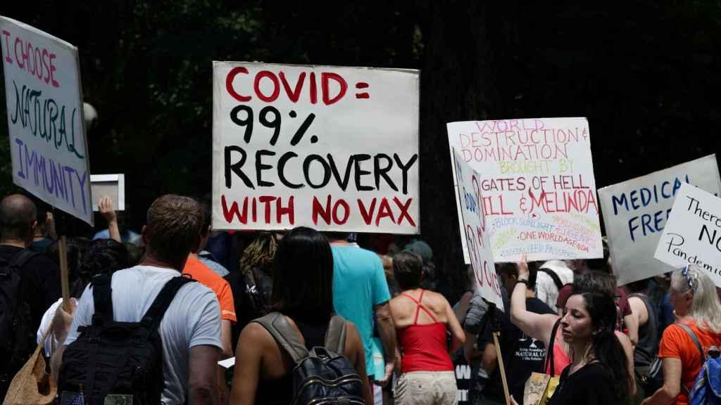 La recuperación del Covid es del 99% sin vacuna, dice la pancarta de unos manifestantes en Nueva York.