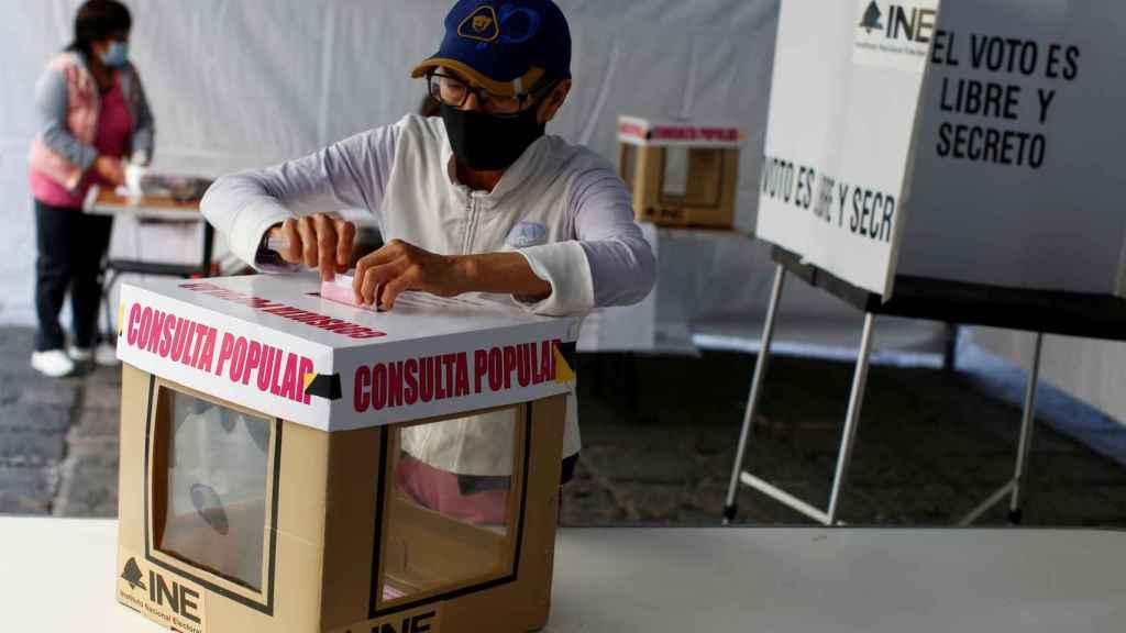 Un hombre depositando su voto en la consulta popular.