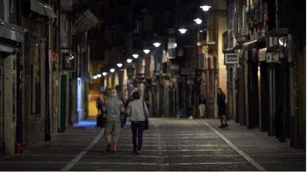 Varias personas caminan por una calle de Pamplona minutos antes del toque de queda.