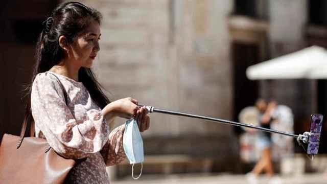 Una turista se hace una fotografía con el teléfono móvil este sábado en el centro de Valencia, durante el fin de semana en el que finaliza julio y da comienzo agosto, muchos empiezan sus vacaciones de verano y otros apuran sus últimos días