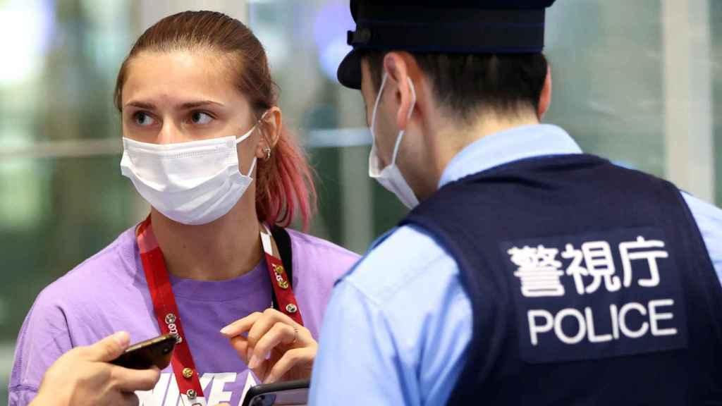 La atleta bielorrusa Krystsina Tsimanouskaya habla con agentes de policía en el aeropuerto de Haneda en Tokio.