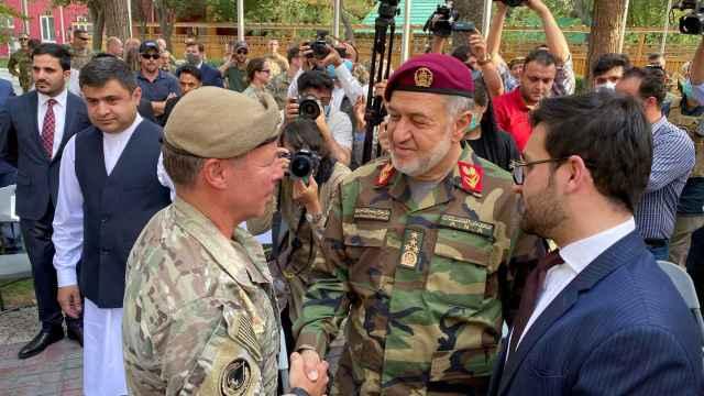 El ministro de Defensa Afgano,Bismillah Khan Mohammadi (d), estrecha la mano del general estadounidense Austin Miller  el día de la retirada de las tropas de EEUU.