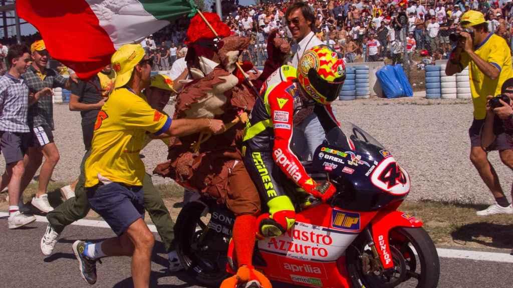Valentino Rossi celebra su victoria en el Gran Premio de Cataluña de 1999 con un pollo subido a su moto.