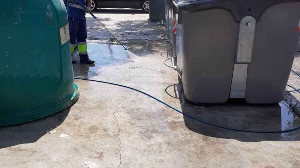 Un operario de limpieza de Málaga baldea junto a varios contenedores de basura.