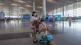 Una mujer empuja un carrito del aeropuerto en el aeropuerto de Pekín.