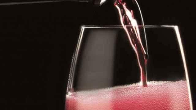 Una persona sirviendo una copa de vino.