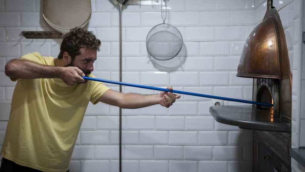 Vittorio Figurato, manipulando el horno donde se hacen sus pizzas artesanales.